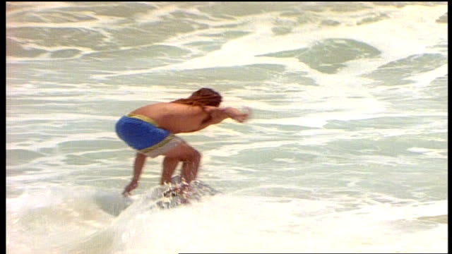 two men running into water and riding skimboard in waves in california - skimboard stock videos and b-roll footage