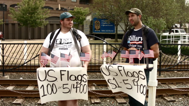 two men sell flags in downtown cleveland at a protrump rally on july 18 2016 in cleveland ohio an estimated 50000 people are expected in cleveland... - republikanischer parteitag stock-videos und b-roll-filmmaterial