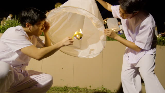 two men setting a flying sky lantern - lantern stock videos & royalty-free footage