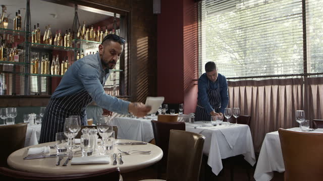 two men setting tables in restaurant - real life stock videos & royalty-free footage