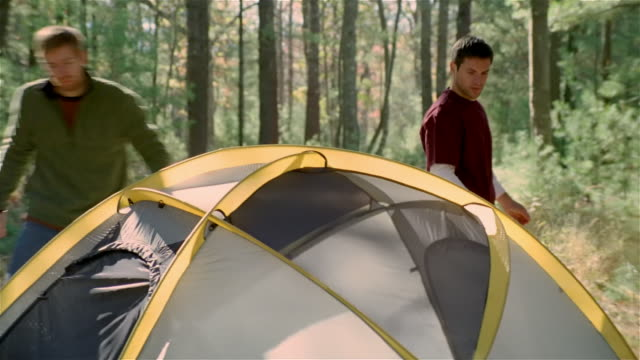 Two men setting up tent at campsite in woods / climbing into tent