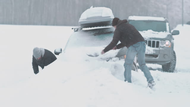 Two men shoveling to dig the car out of snow