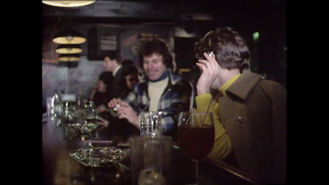 stockvideo's en b-roll-footage met two men sit at a bar smoking in new york;1976 - bar tapkast