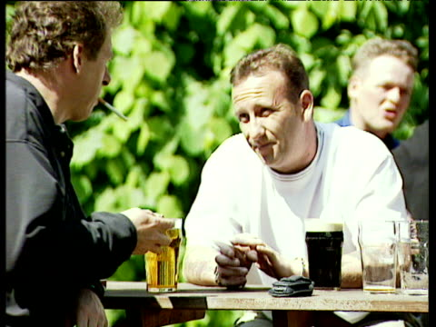 vídeos de stock, filmes e b-roll de two men sit at table outside public house with drinks and smoking cigarettes england - abuso de substâncias