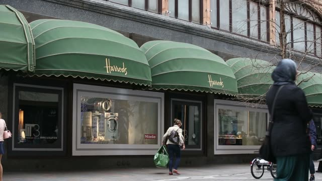 Two men sit on a bench with branded shoppings bags outside the Harrods luxury store in the Knightsbridge district of London UK on Thursday April 3...