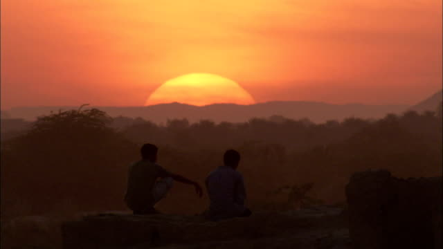 two men sit on a rocky wall and gaze at a glowing orange sun in the shibam desert. - yemen stock videos & royalty-free footage