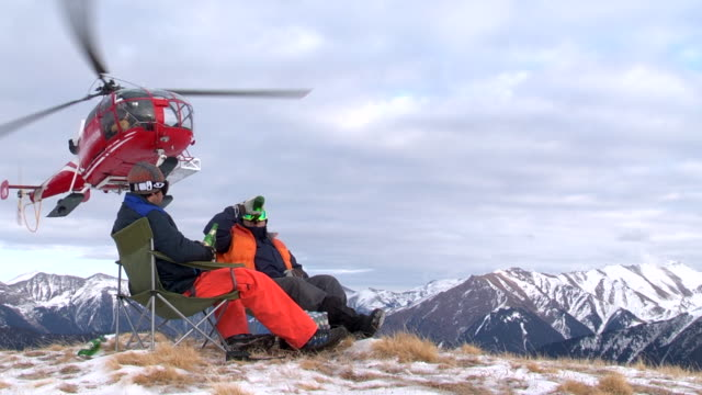 two men sit on the top of a mountain as a helicopter drops off supplies. - helicopter tour stock videos and b-roll footage