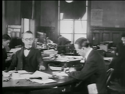 B/W 1927 two men sitting at desk / one smokes cigarette / one writes on paper (newspaper office?)