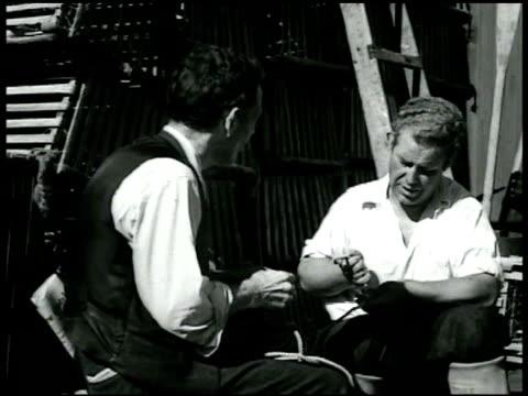 vídeos de stock e filmes b-roll de two men sitting by water boat bg mending fishing net men sitting by fireplace talking crowd along shoreline ws president franklin d roosevelt on... - 1935