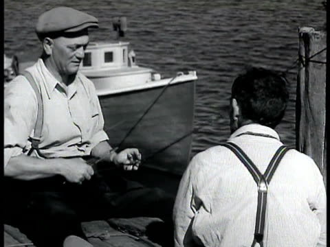 two men sitting by water boat bg mending fishing net men sitting by rotting boat on beach - 1935 stock videos and b-roll footage
