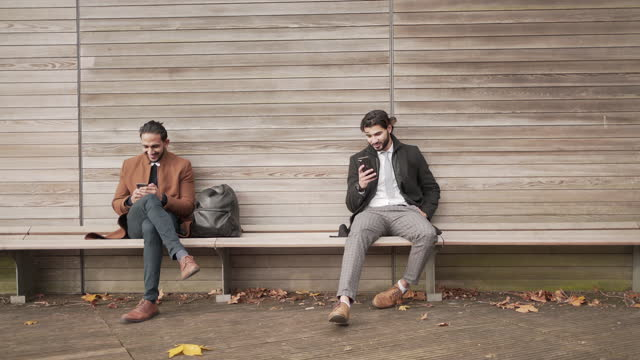 two men sitting down on a park bench - sitting stock videos & royalty-free footage