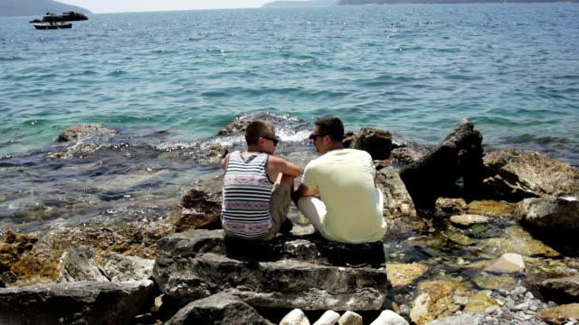 two men sitting near the sea - rocky coastline stock videos & royalty-free footage