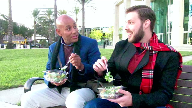 two men sitting on bench eating lunch, talking - debate stock videos & royalty-free footage