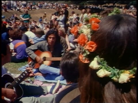 1968 two men sitting on ground playing acoustic guitars / woman in flower headband in foreground / ca - 1968年点の映像素材/bロール