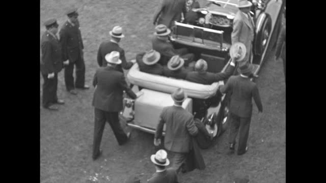 two men sitting on seats in stands other people leaving / overhead shot of pres franklin roosevelt in back seat of open car leaving stadium / crowd... - eastern usa stock videos and b-roll footage