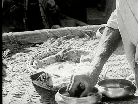 two men sitting outside on mat wearing turbans eating with hands, woman brings over small bowls of food, man taking food with fingers placing it on... - 敷物 マット点の映像素材/bロール