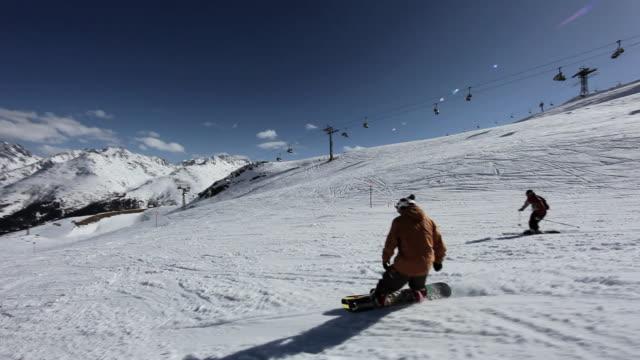 two men snowboarding and skiing in ski resort - bastoncino da sci video stock e b–roll