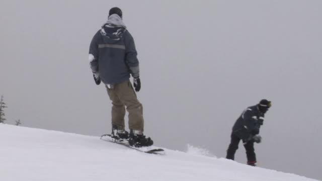 vídeos de stock e filmes b-roll de slo mo, ws, pan, two men snowboarding, whitefish, montana, usa - roupa de esqui
