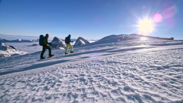 Two men snowshoeing across a mountain in sunshine