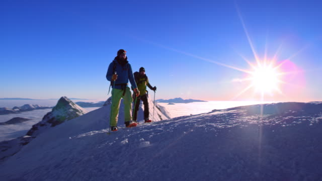 Two men snowshoeing on mountain top in sunshine