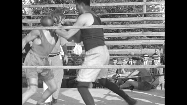 stockvideo's en b-roll-footage met two men spar in outdoor ring as men and boy spectators look on / note exact year not known documentation incomplete - kleding
