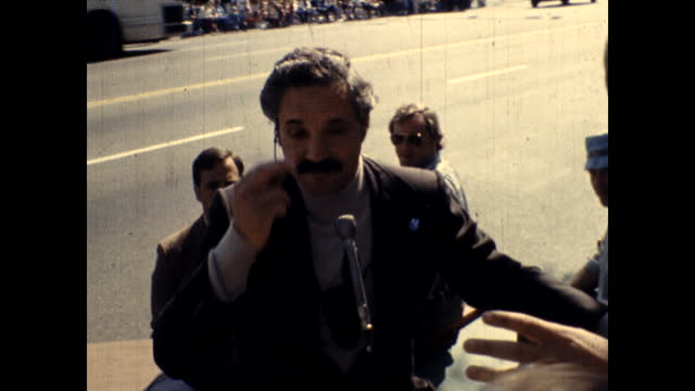 vidéos et rushes de two men speak to each other into microphones sitting at a table in a crowd. hal linden being interviewed. close ups of people in a crowd, many... - micro