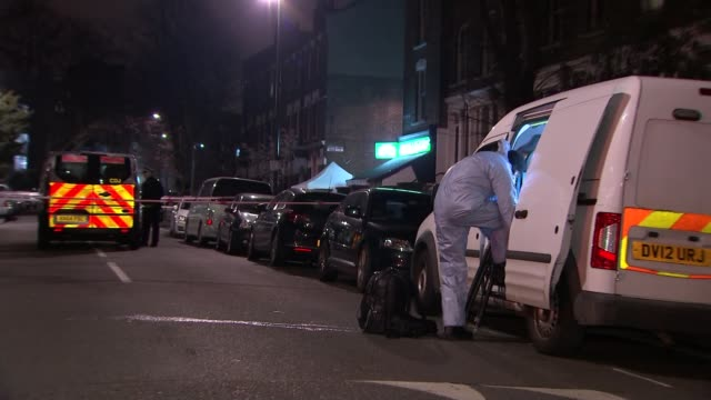 stockvideo's en b-roll-footage met two men stabbed to death in camden england london camden kentish town forensic tent at crime scene pull out forensic officer putting on shoes by van... - kentish town