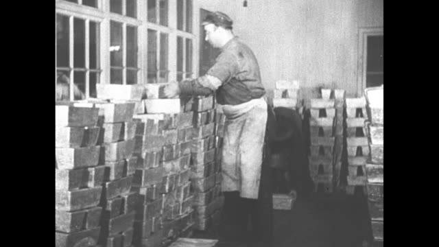 ms two men stack hundreds of silver bars / man holds silver bar at waist level and turns it / note exact day not known - ingot stock videos & royalty-free footage