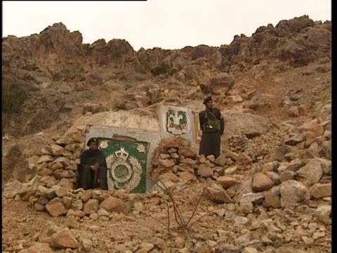 two men stand beside old regimental emblems on the side of a rock face - rock face stock videos & royalty-free footage
