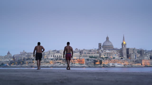 Two men stand on shore of Valletta, Malta - UNESCO World Heritage Site