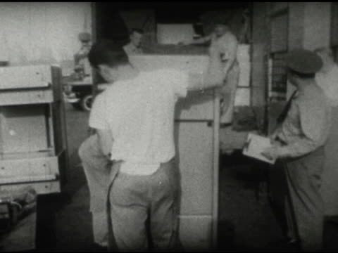 / two men stand, one holds typewriter and other wears police-guard cap and clipboard on january 01, 1959 - 1959 stock videos & royalty-free footage