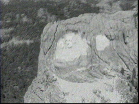 vidéos et rushes de two men standing at the opening of a tunnel with mount rushmore in the distance / a line of planes flying above the monument / aerial footage of... - monument national du mont rushmore