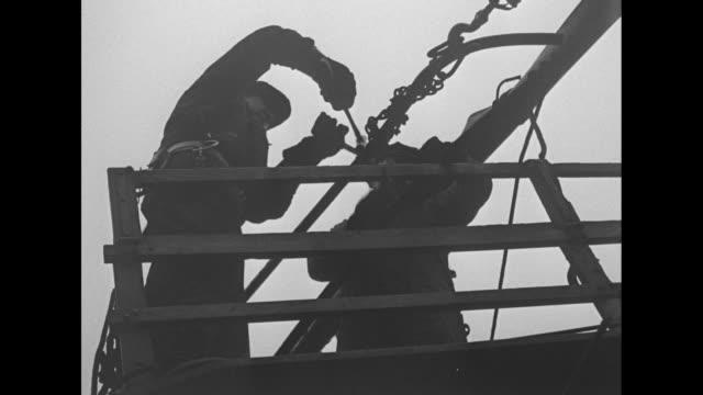 vídeos y material grabado en eventos de stock de two men standing beside repair truck underneath railroad bridge two men above in wooden scaffold on side of bridge / two shots from below of two men... - balancearse