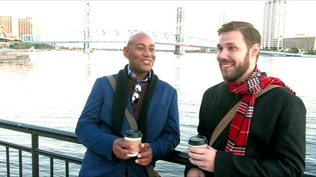 Two men standing on city waterfront, talking