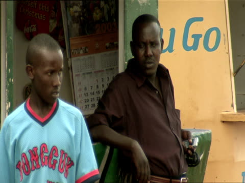 ms two men standing outside of shop / nyamirambo, kigali, rwanda - キガリ点の映像素材/bロール
