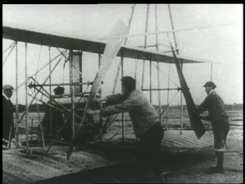 B/W 1903 two men starting propellers of early Wright brothers' airplane