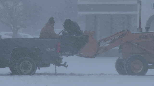 Two men struggle to off load a very heavy piece of equipment onto a fork lift during an intense blizzard in Waterbury Connecticut