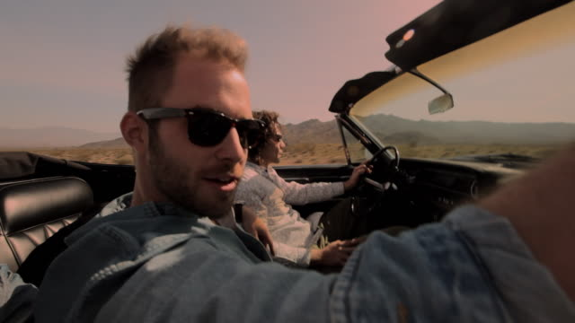vídeos y material grabado en eventos de stock de two men take a road trip through the desert in a vintage convertible. - amistad masculina