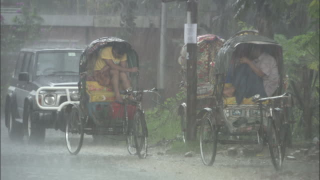 vídeos de stock e filmes b-roll de two men take shelter in rickshaws during a monsoon. available in hd. - monção