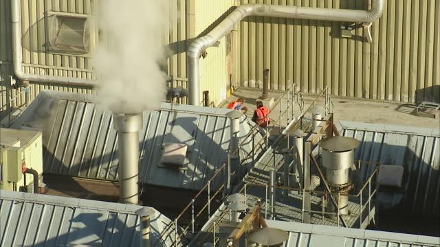 stockvideo's en b-roll-footage met two men taking a break on an industrial roof - schoorsteen