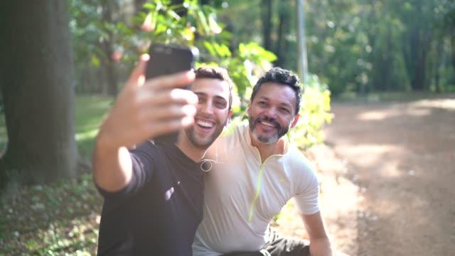 zwei männer, die ein selfie im park machen - 50 54 jahre stock-videos und b-roll-filmmaterial