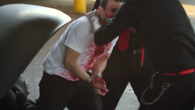 MS Two men taking handcuffed and bloodied man out of car trunk / Jacksonville, Florida, United States