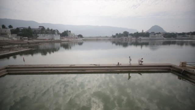 Two men talk in the distance by Pushkar Lake