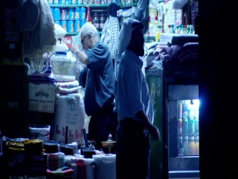 stockvideo's en b-roll-footage met two men talk outside a street vendor's doorway at night. - men