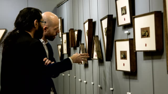 two men talking about a brass engraving - exhibition stock videos & royalty-free footage