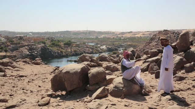 Two men talking at the top of a mountain with the view of the Nile River and a Nubian Village