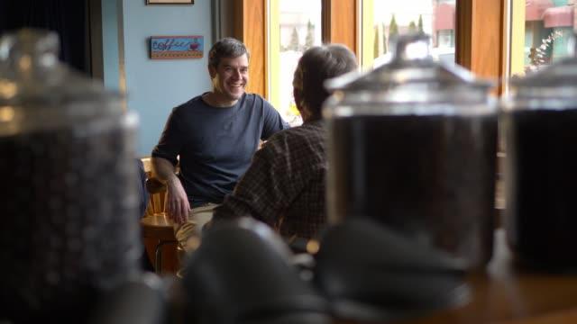 vídeos de stock e filmes b-roll de two men talking in a coffee shop - bar local de entretenimento