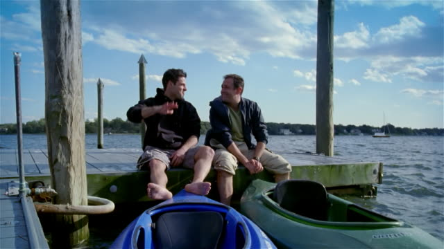 vídeos de stock e filmes b-roll de two men talking while sitting on dock with kayaks in water / high fiving - pontão
