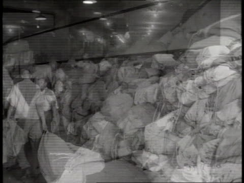 two men throw sacks of mail in a pile while postal workers sort and stamp mail. - post office stock videos & royalty-free footage