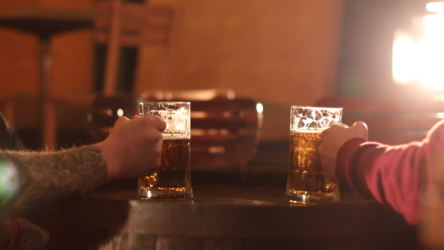 Two men toasting with beer at the pub